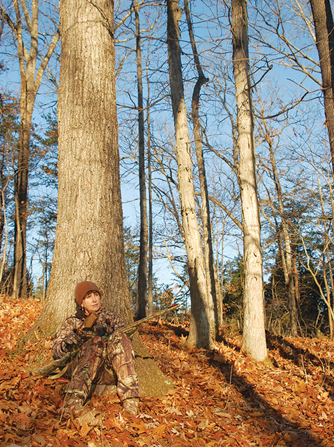 hunting turkey in a fall woods, leaning against a large tree calling turkey